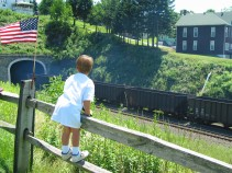 The View from the Park: A youngster enjoys the view of an empty coal train emerging from the Allegheny Tunnel.